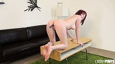 Gorgeous redheaded bimbo fucks herself hard on top of a desk
