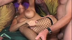 Buxom blonde in black fishnet stockings Trina Michaels has fun with two big cocks