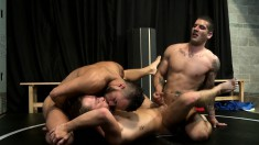 Hunky wrestling coach gets pinned to the mat in a hot M2M threesome