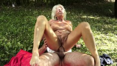 Busty blonde cougar has a stiff cock punishing her sweet holes outside